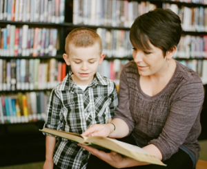woman reading book with little boy